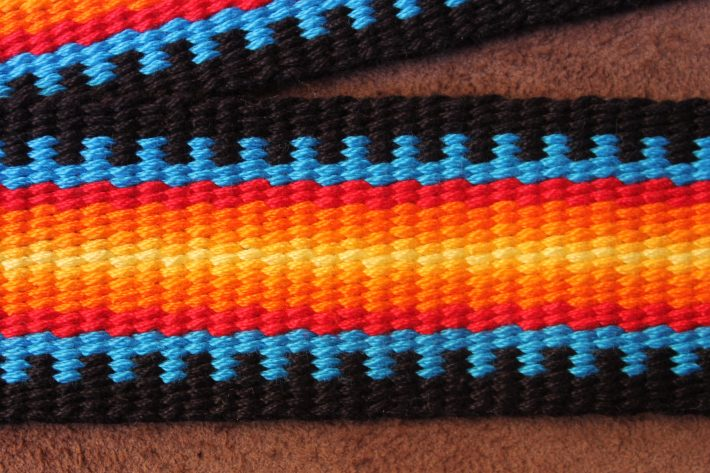 "Handwoven Guitar Strap, handwoven in bright reds, oranges and yellows and turquoise blue. Title ""Heat of the Flame"""